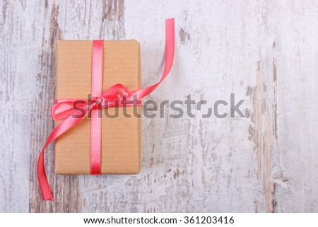Wrapped gift for Valentines day, birthday or other celebration on old wooden white table, copy space for text - stock photo