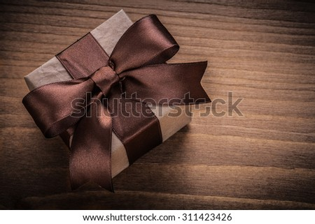 Wrapped gift on vintage wood board horizontal view holidays concept.