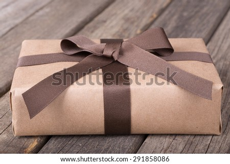 Wrapped gift package on old wood surface - stock photo