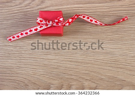 Wrapped gift with red ribbon on wooden background, decoration for Valentines Day, copy space for text - stock photo