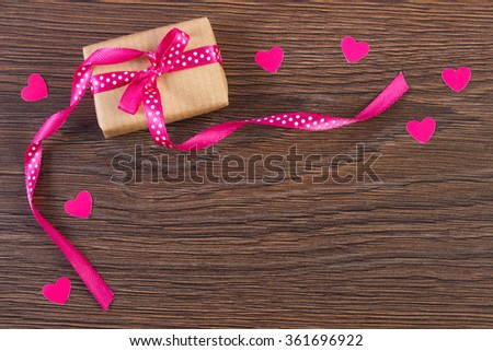 Wrapped gift with ribbon and valentine hearts on wooden background, decoration for Valentines Day, symbol of love, copy space for text - stock photo