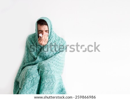 wrapped in the warm turquoise knitted blanket, sick, bearded man with a red nose snotty blowing his nose into a handkerchief - stock photo