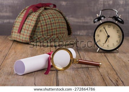 Wrapped paper sheets and magnifying glass on Old Wooden table. - stock photo