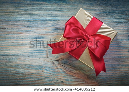 Wrapped present box on vintage wooden board top view holidays concept. - stock photo