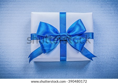 Wrapped present box with bow on blue background holidays concept. - stock photo