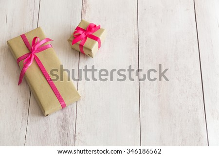 Wrapped presents gifts boxes in brown natural wrapping paper with pink and pink and white polka dot ribbons on off white wooden background with free space - stock photo
