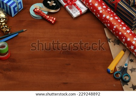 Wrapping Christmas gift - preparation. Accessories on wooden desk, top view - stock photo