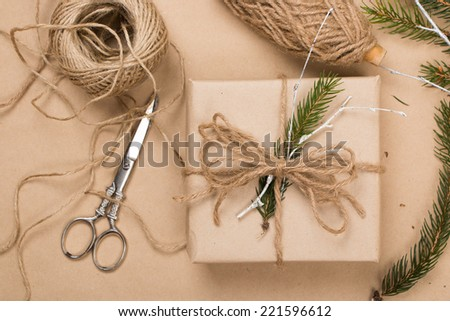 Wrapping eco Christmas packages with brown paper, string and natural fir branches  - stock photo