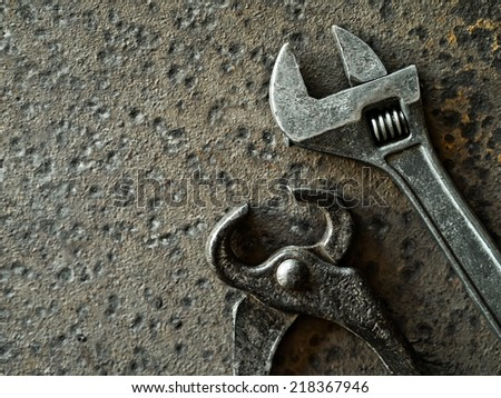 Wrench and pincers over a rusty metal background - stock photo