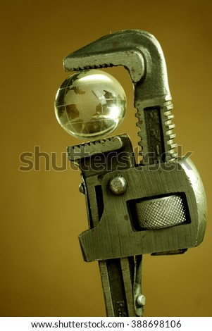 Wrench holding a glass globe-Concept of world and issues - stock photo