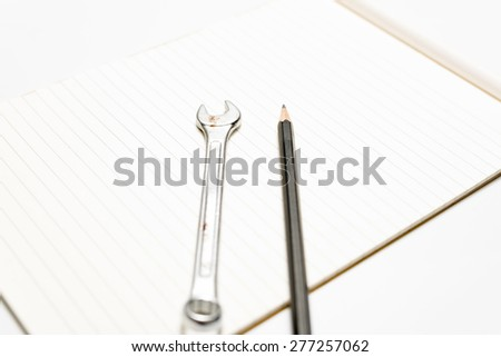 wrench with pencil on notebook
