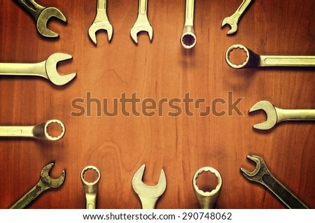 Wrenches frame. Wrenches and ring spanners in several different sizes on natural wooden background. - stock photo