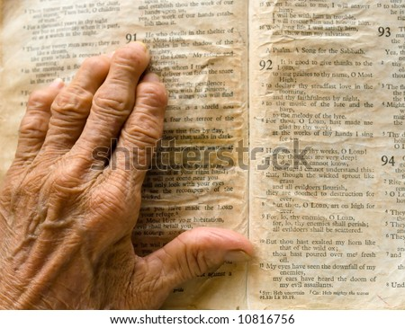 Wrinkled, Arthritic hand of an old woman on an old, yellow, worn out bible turned to the page of Psalm 91.
