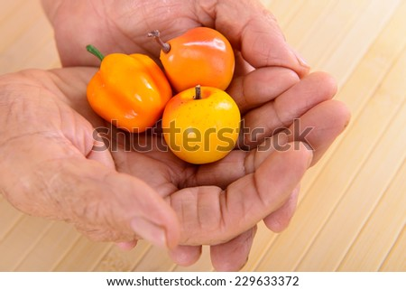 wrinkled hands of old woman keep fruit - stock photo