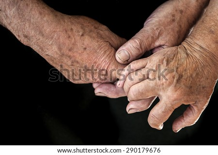 Wrinkled hands of two old elderly people holding each other closeup on black background, horizontal picture