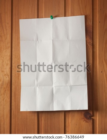 Wrinkled paper on wood wall - stock photo