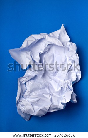 Wrinkled white piece of paper over a blue background. - stock photo