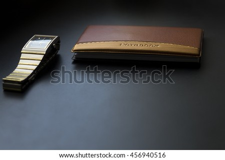 wrist watch and notebook on black background
