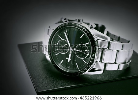 Wrist watch with stainless steel on black box on white background. Black and white color. Copy space. Selective focus.
