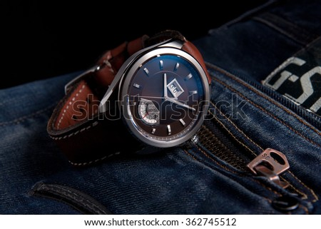 Wrist watches on brown leather strap on blue jeans - stock photo