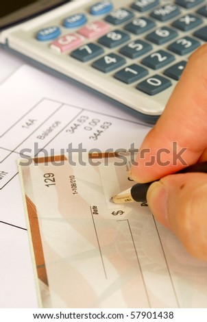 Write a check to pay the bills - stock photo