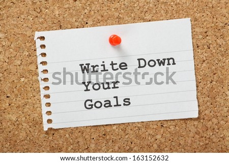 Write Down Your Goals typed on a scrap of paper pinned to a cork notice board. Writing down goals helps to make them more real and will provide focus as you plan the steps to reach them. - stock photo