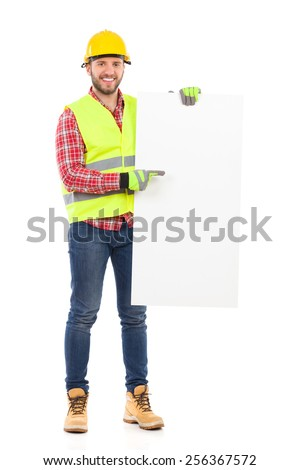 Write something on this white board. Manual worker in yellow helmet and reflective waistcoat holding white placard and pointing. Full length studio shot isolated on white. - stock photo