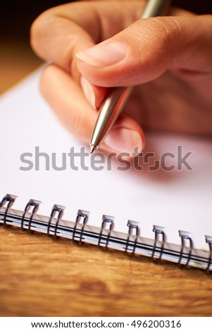 write with a pen in a notebook business woman
