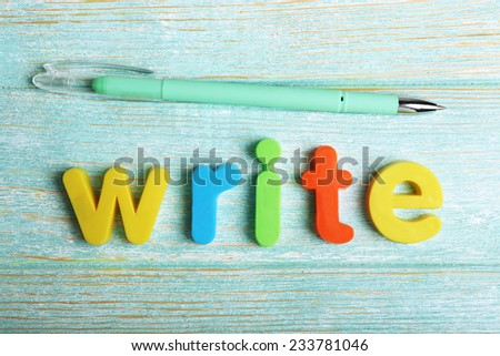 Write word formed with colorful letters on wooden background - stock photo
