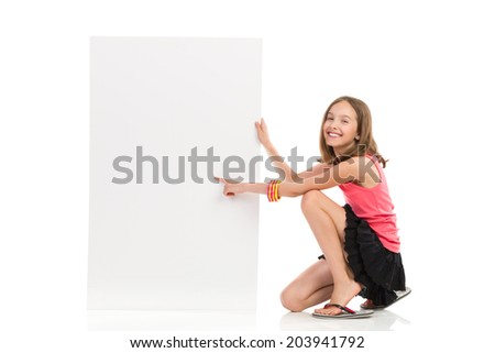 Write your message on blank banner. Cute girl crouch near blank banner and pointing. Full length studio shot isolated on white. - stock photo