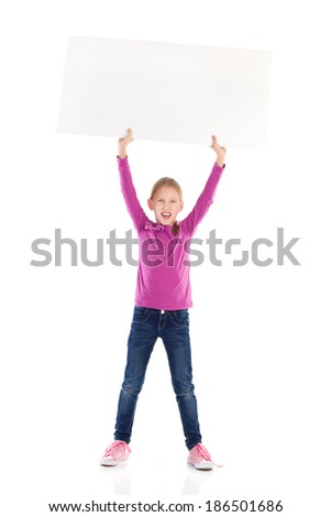 Write your message on white banner. Cute little girl holding blank banner over her head and shouting. Full length studio shot isolated on white. - stock photo