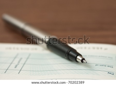 Writing a cheque- very shallow depth of field with focus of tip of pen - stock photo