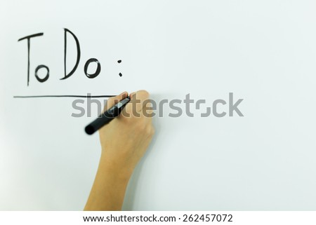 writing a To Do list onto a white writing board - stock photo