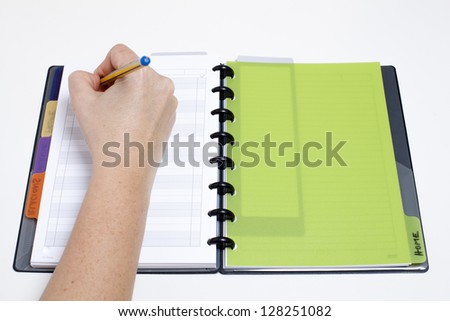 Writing appointments on agenda/Scheduling the day - stock photo