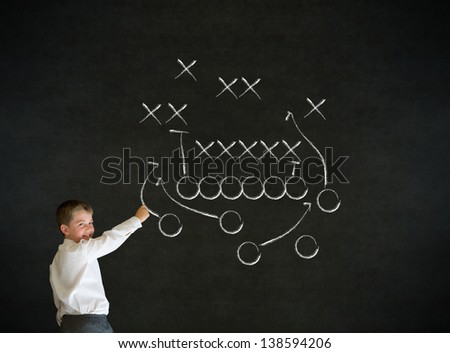 Writing boy dressed up as business man with chalk American football strategy on blackboard background - stock photo