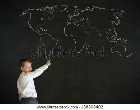 Writing boy dressed up as business man with chalk geography world map on blackboard background - stock photo