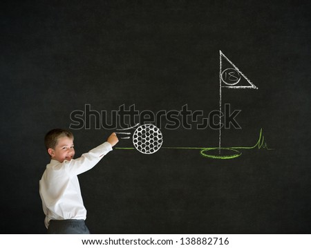 Writing boy dressed up as business man with chalk golf ball flag green on blackboard background - stock photo