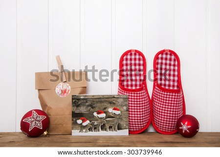 Writing christmas cards and making handmade presents. Wooden background with red and white decoration. - stock photo