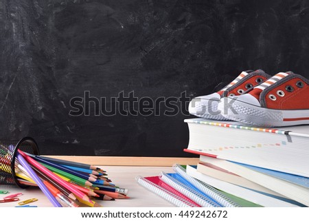 Writing desk with school tools on wood table and blackboard in the background with place left for title. Front view - stock photo