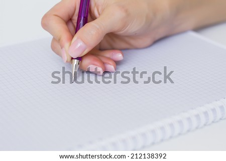 Writing down notes in paper notepad - stock photo