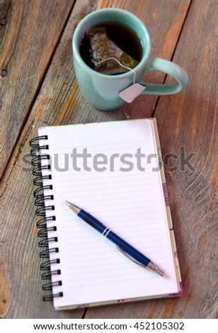 Writing down thoughts in an empty journal with a cup of tea - stock photo