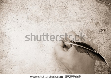 writing hand and pen feather on background texture - stock photo