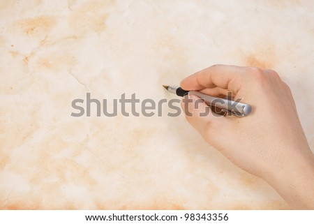 writing hand with ink pen on old paper parchment background - stock photo