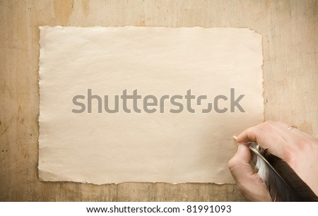 writing hand with pen feather on wood background - stock photo