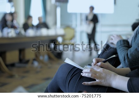 Writing in a notebook at the conference, tinted. - stock photo