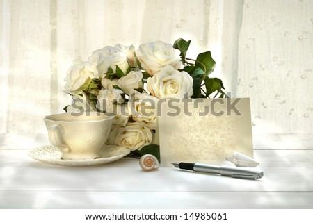 Writing invitation card with pen and a cup of tea - stock photo