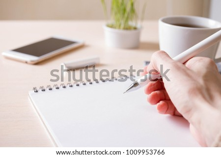 Writing on an empty notepad with pen and other accessories on a wooden table