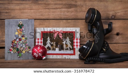 Writing or calling friends on christmas time. Wooden background with greeting cards and an old nostalgic phone. - stock photo