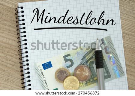 Writing pad with money and the german word minimum wage / minimum wage - stock photo