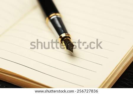 Writing pen on notebook background - stock photo